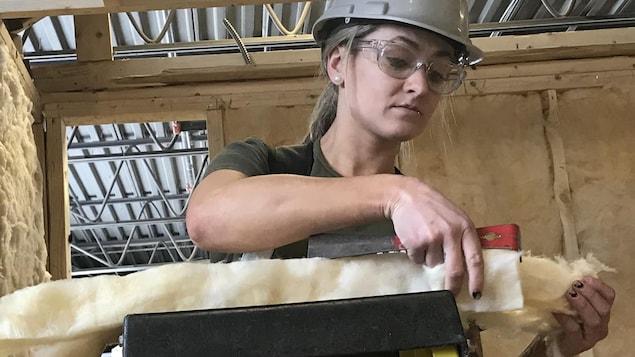 Marie-Ève Lebeau, élève en menuiserie-charpenterie au Centre de formation professionnelle 24-Juin découpe de la laine minérale pour examen pratique d'isolation de murs.