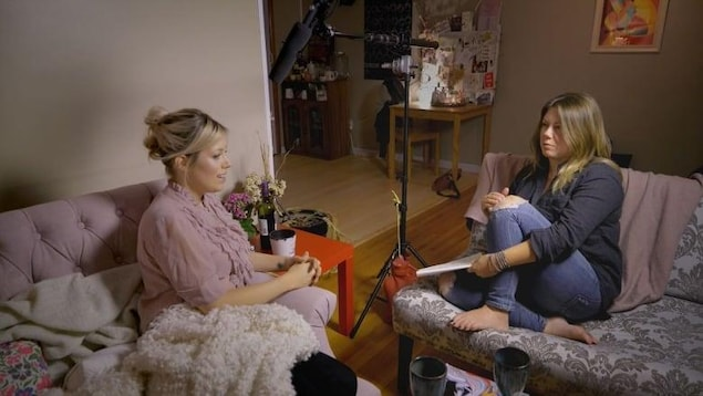 Marie-France Guerrette, assise sur un canapé, fait une entrevue avec une femme dans une scène de son film.