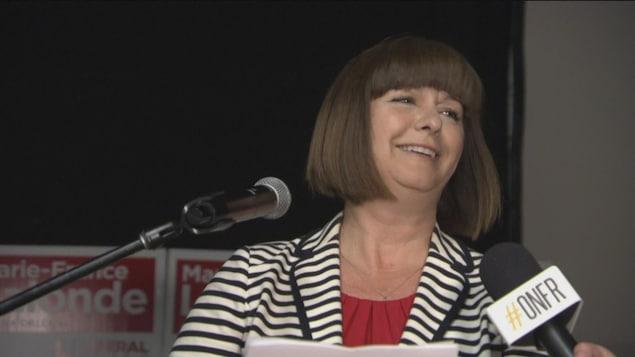Marie-France Lalonde est debout devant un micro dans une salle.