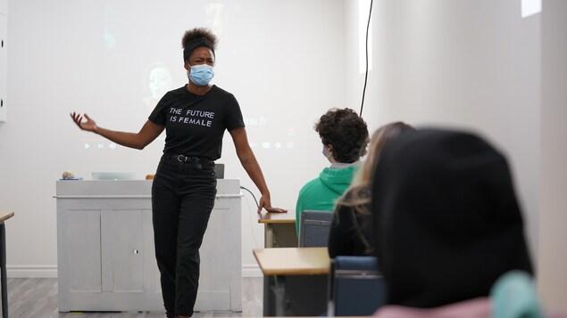Marie-Luce Béland devant une classe qui parle avec un masque.