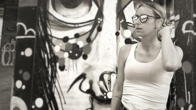 Portrait en noir et blanc de Marie St-Hilaire-Tremblay, de trois-quarts, en extérieur, devant une murale. Elle porte des lunettes de soleil miroir, une camisole blanche, et a la main gauche relevée derrière son oreille et a un tatouage sur l'intérieur de l'avant-bras droit.