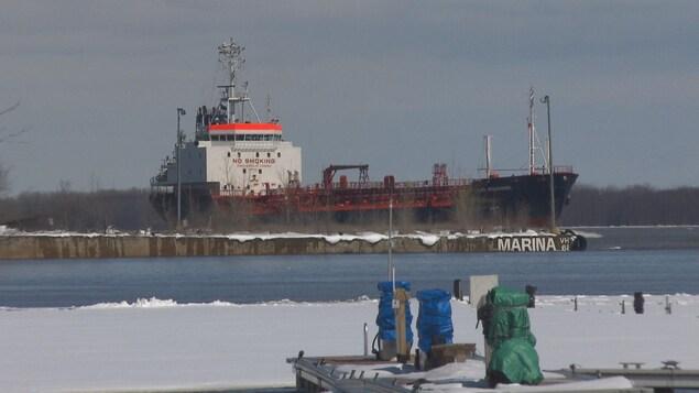 Un bateau-cargo passe sur le fleuve devant la marina de Trois-Rivières.