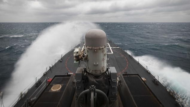 Le USS John S. McCain, un destroyer à missiles guidés de la marine américaine, provoque des gerbes d'eau en naviguant en mer.