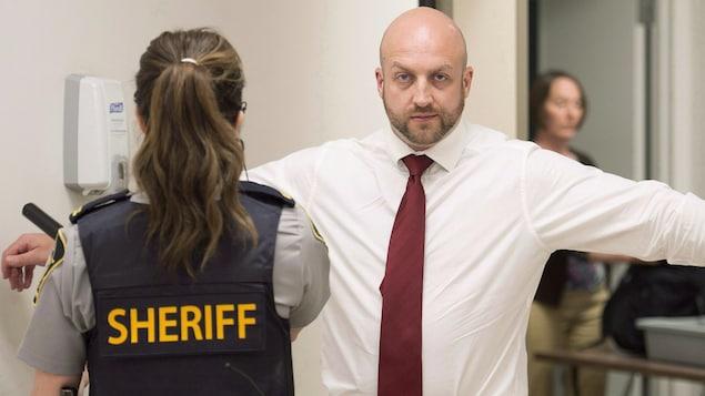 Darren Smalley est fouillé par une policière à son entrée en cour provinciale.