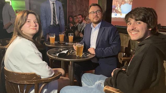 Mario Simard est assis avec des partisans.