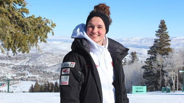 Marion Thénault sourie à la caméra, dehors devant une montagne.