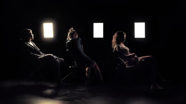 Trois femmes sont assises sur des chaises pliables sur scène. Le décor est sombre et trois lumières rectangulaires éclairent légèrement leurs silhouettes.