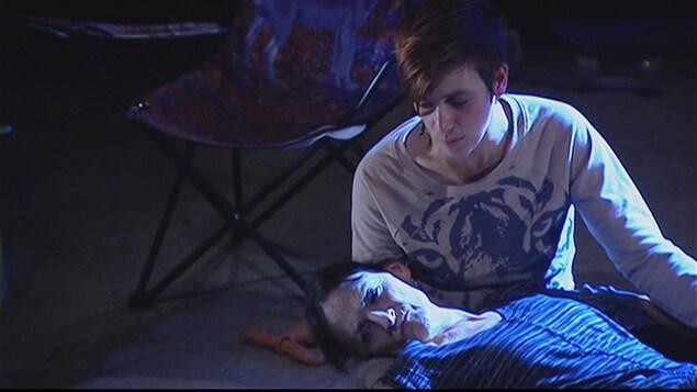 Micheline Marin et Marjolaine Beauchamp dans la pièce « Taram ». Une femme âgée est couchée sur le sol les yeux ouverts. Une jeune femme assise par terre veille sur elle.