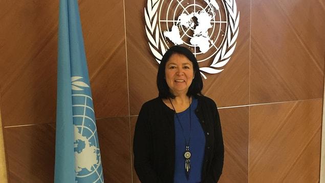 Une femme autochtone pose devant un logo et un drapeau de l'ONU.