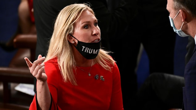 Marjorie Taylor Green, parlant à quelqu'un, la main levée, portant  sous sa bouche son masque, sur lequel on distingue le mot « Trump ».