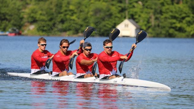 Les quatre kayakistes pagaient en harmonie à bord de leur embarcation, sur un plan d'eau tranquille.