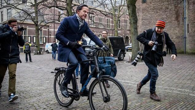 Mark Rutte est pourchassé par des photographes alors qu'il circule à vélo, une pomme en main.