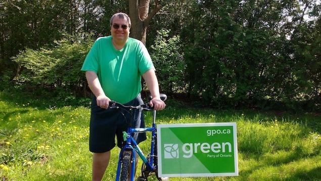 Mark Vercouteren pose à côté d'une bicyclette et d'une pancarte du Parti vert du Canada.