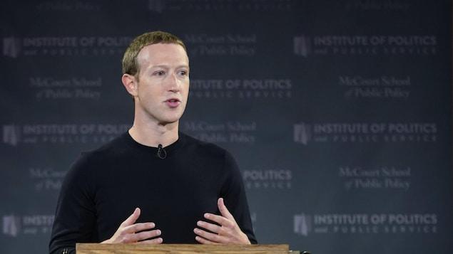 Mark Zuckerberg, debout derrière un lutrin en bois, s'adresse à une foule.