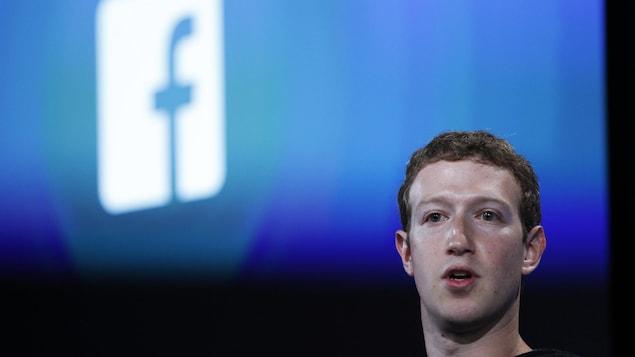 Le fondateur de Facebook devant le logo de son entreprise