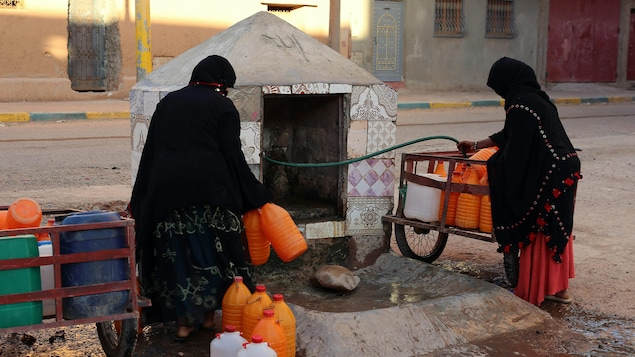 Femmes marocaines remplissant des contenants d'eau dans le sud du Maroc.