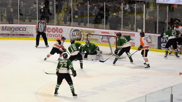 Deux équipes s'affrontent sur la glace. La photo est prise devant le but où le gardien des Marquis fait un arrêt.