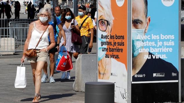 Des piétons portant un masque dans le Vieux-Port à Marseille