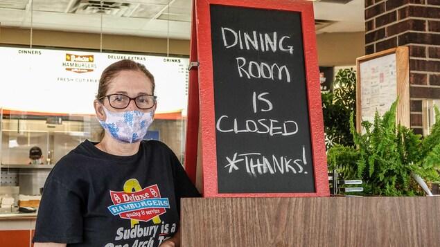 Marsha Smith à côté d'une affiche qui indique que la salle à manger est fermée.