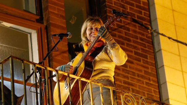 Martha Wainwright devant un micro et avec une guitare sur un balcon.