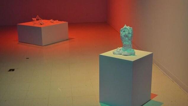 Une oeuvre en posée sur un cube dans une salle d'exposition.