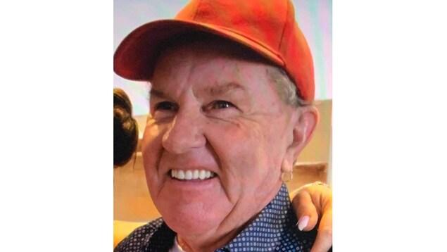 Le visage de l'homme, qui sourit, avec une casquette.