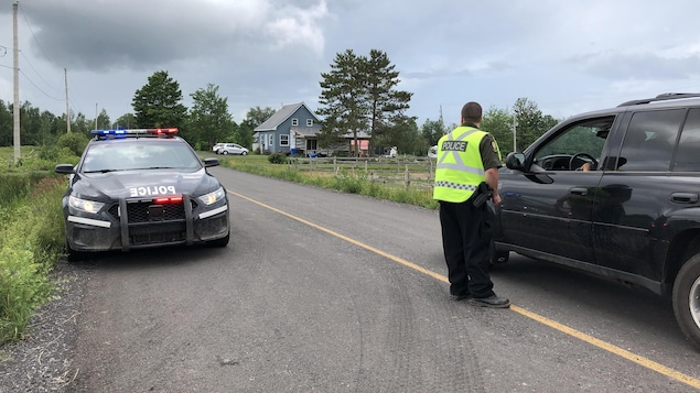 Un policier parle à un citoyen dans une voiture.