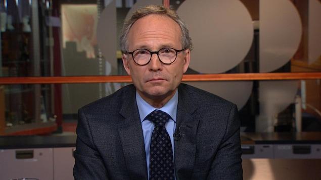 Un homme portant des lunettes ovales semble nous regarder droit dans les yeux. Il porte un veston-cravate et il a les cheveux grisonnants.