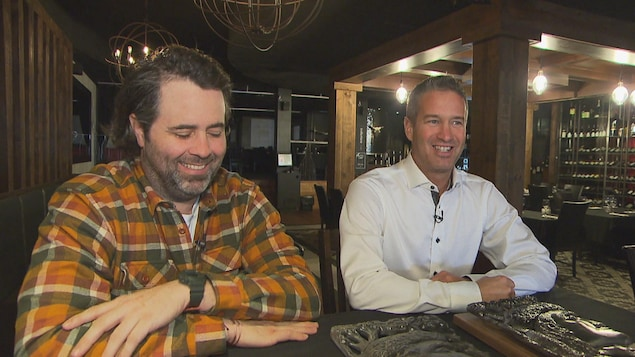 Les deux hommes, souriants, assis à une table du restaurant.