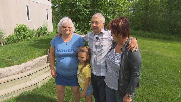 Martin Villeneuve entouré de sa femme, sa belle-soeur et sa petite-fille dans sa cour arrière.