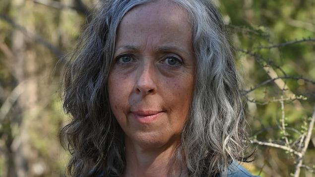Portrait en couleur, en extérieur. La femme regarde la caméra. Elle a les cheveux gris, mi-longs, et lâchés.