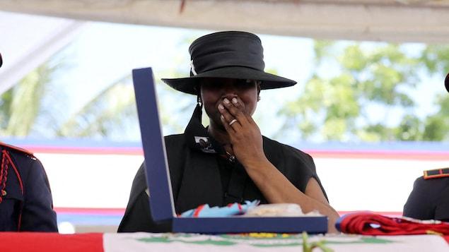 Martine Moïse, habillée en noir, porte une main à sa bouche devant un cercueil recouvert d'un drapeau haïtien.