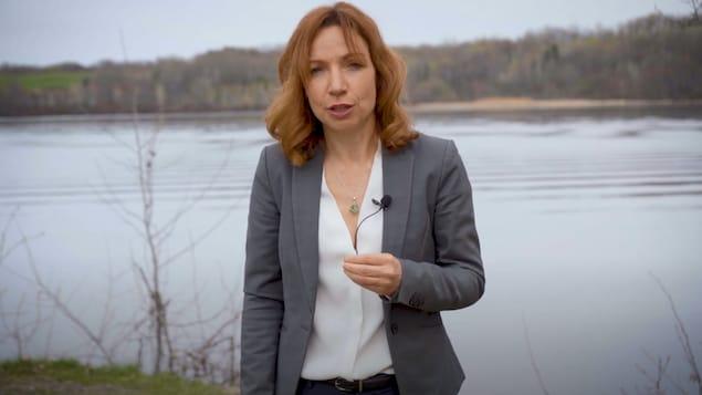 Une femme en veston se tient devant un lac.
