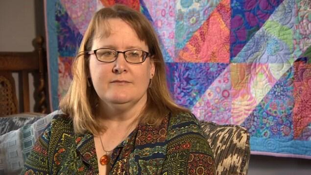 Mary-Anne Parker, assise dans son salon, regarde la journaliste lors d'une entrevue.
