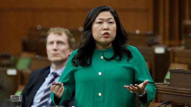 La ministre Mary Ng est debout à la Chambre des communes. On voit derrière elle son collègue Marc Miller