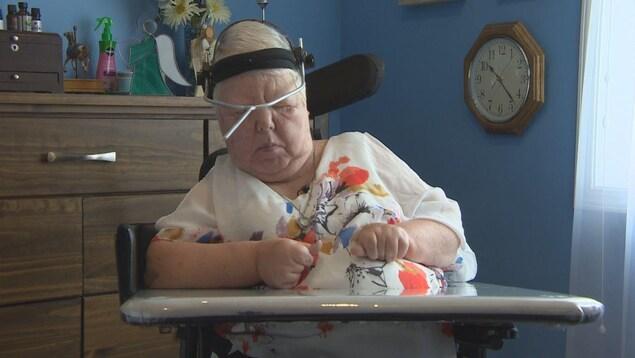 Mary Scott assise à sa chaise, portant un manche de pinceau sur son front.