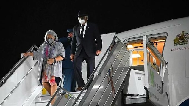 Un homme et une femme descendent les marches d'un avion.
