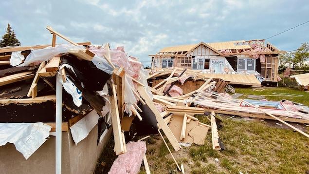 Des débris jonchent le sol devant une maison endommagée.