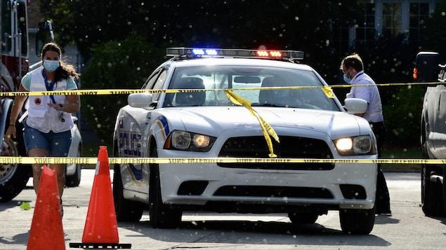 Des gens empressés se trouvent près d'une voiture de police stationnée.
