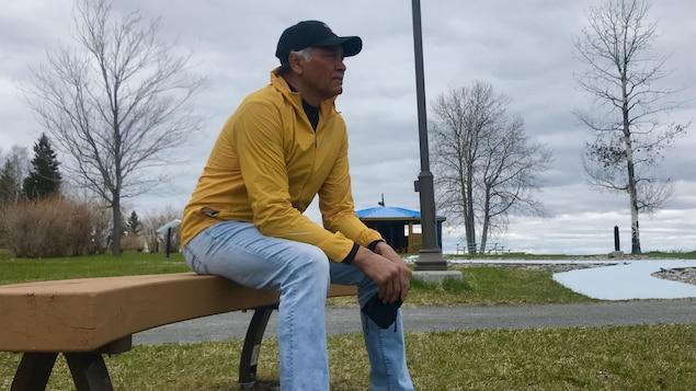 Un homme est assis sur un banc dans un parc et regarde au loin.