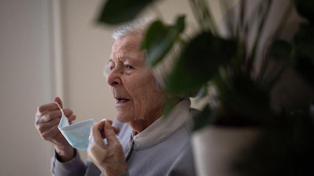 Une femme âgée s'apprête à mettre son masque contre la COVID-19.