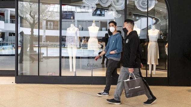 Deux jeunes se promènent dans un centre commercial et portent un couvre-visage.