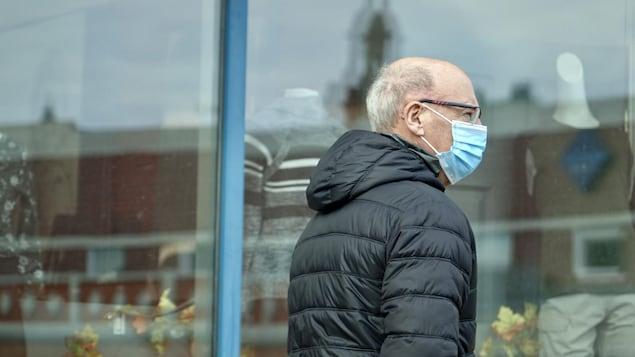 Un piéton portant un masque.