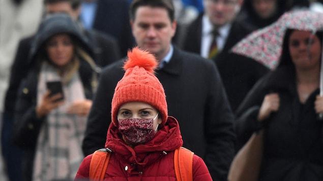 Une femme dans la foule avec une tuque à pompon et un masque rouge couvrant sa bouche et son nez.