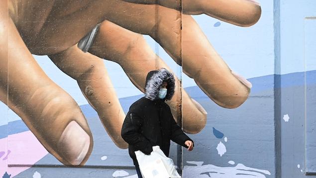 Un passant masqué marchant devant une main gigantesque sur une  fresque murale.