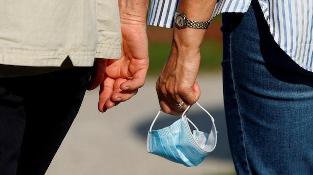 Les mains d'un couple qui marche dans une rue.