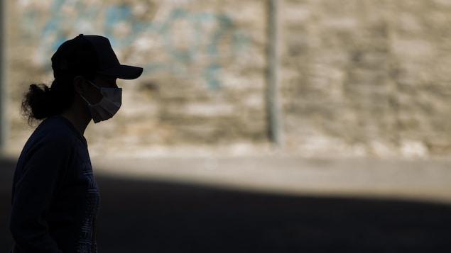 Le profil d'une personne qui porte un masque et une casquette.