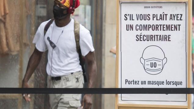 Une pancarte demande aux clients du magasin de porter un masque.
