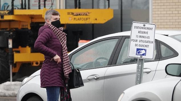Une femme portant un masque s'apprête à entrer dans sa voiture dans le stationnement d'un commerce.