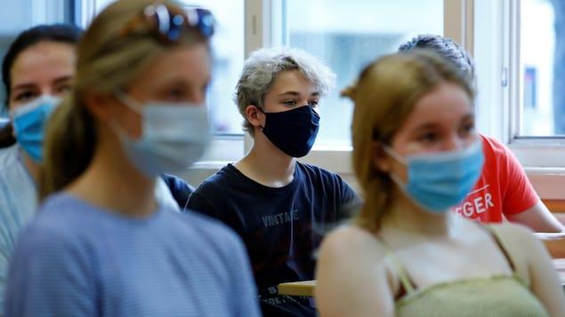 Des adolescents sont assis à leur pupitre dans une salle de classe. Ils portent tous un masque non médical sur le visage.